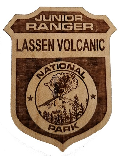 Wooden ranger badge with erupting volcano