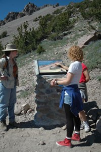 Hikers read an interpretive panel on the Lassen Peak Trail