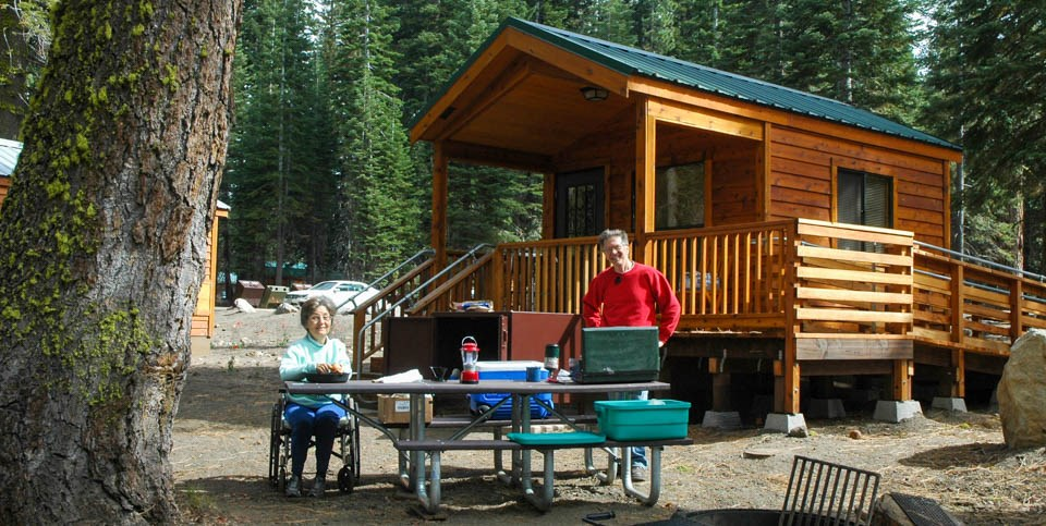 A man stands and a woman sits in a wheelchair at either end of a picnic table in front of a wooden cabin with an access ramp.