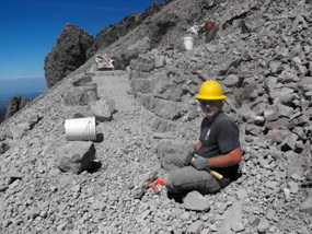 A trail crew member prepares to place a stone on a steep switchback