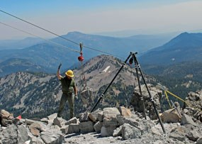 A trail worker guides a boulder on a pulley system