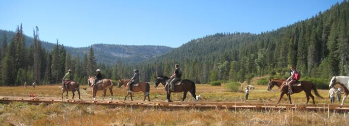 Horseback riders cross a new boardwalk that permits natural water flow in the restored Drakesbad Meadow.