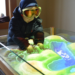 A boy plays with an augment reality sandbox