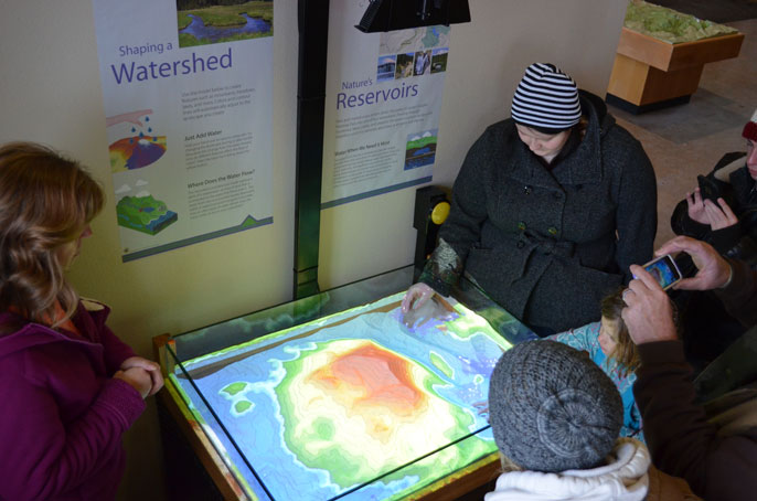 Visitors play with an augmented reality sandbox