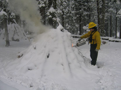 A park firefighter uses a drip torch to hand ignite a burn pile