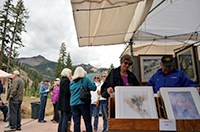 Visitors peruse paintings on a patio