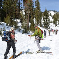 A man skis past another man holding a beacon out toward him