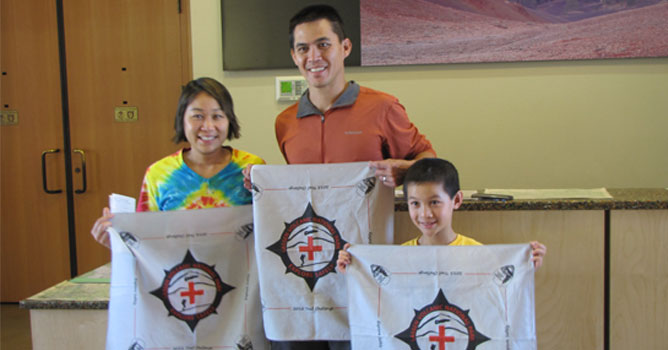 Explore Safely trail challenge participants display their challenge bandanas.