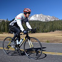 A bicyclist rides on the park highway with a meadow and snow-covered peak in the background
