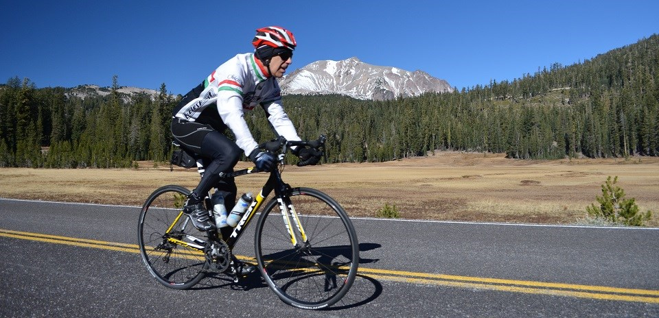 A man rides a road bike on a road in front of a meadow and gray mountain