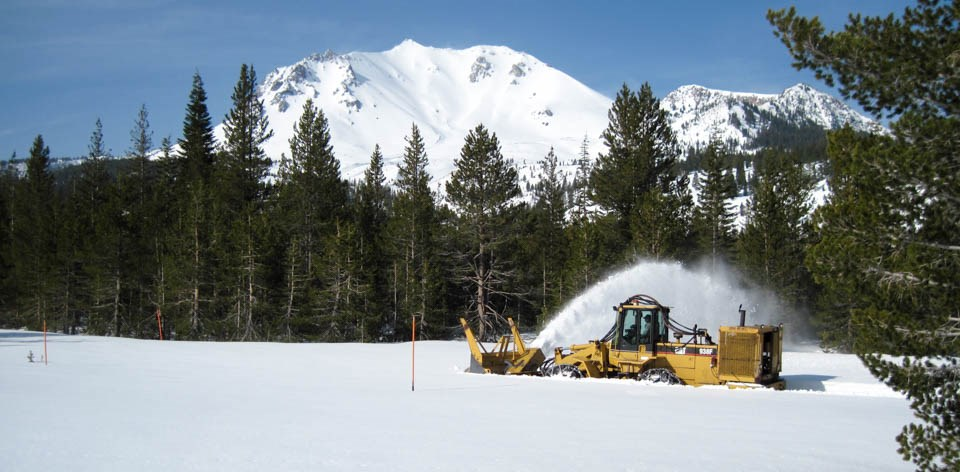 A yellow snowplow clears snow backed by a snow-covered mountain