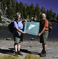 Hikers holding a trail challenge bandana