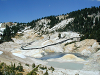 View of Bumpass Hell boardwalk winding through thermal areas with grey and yellow thermally altered earth.