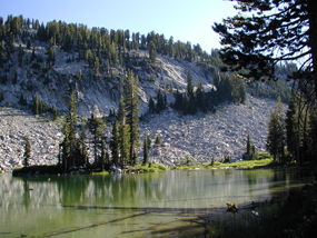 view of emerald green cliff lake with trees reflecting on calm water and rocky reading peak in the background.