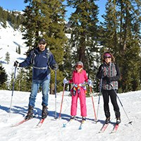 A family poses on cross-country skis