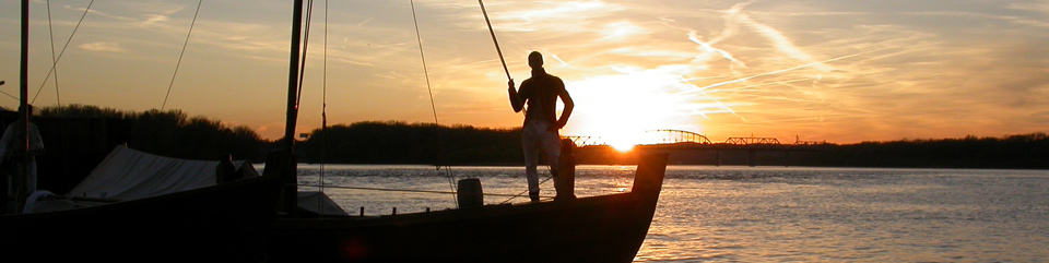 photo of a replica keelboat with a crew member on the bow at sunset