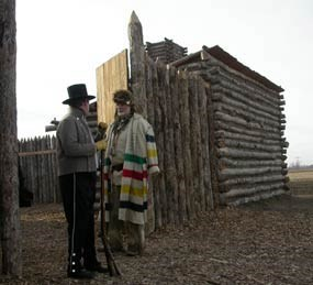 Reenactors stand outside of replica of Camp Dubois, a log fort.