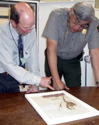 Uniformed NPS ranger and staff member from the Academy of Natural Sciences look at plant specimen collected by Meriwether Lewis.