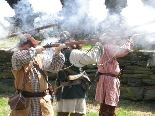 Reenactors dressed in period clothing fire rifles as gun smoke hangs in the air.
