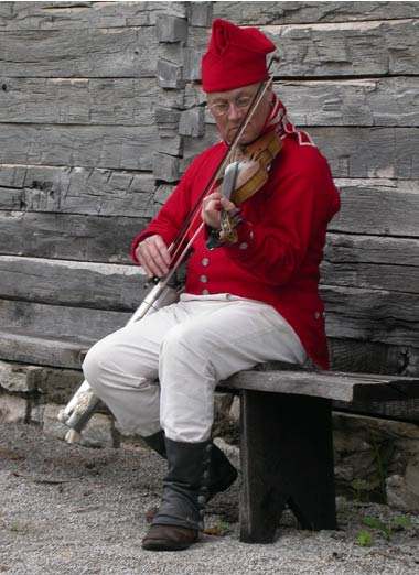 Fiddler, in red coat and hat, playing at Fort Osage.