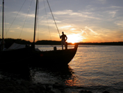 Reenactor standing in a boat on the Missouri River at sunset.