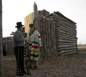 Reenactors in period clothing stand outside a replica of Camp Dubois, a log fort.
