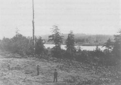 Historic photo of the Fort Clatsop site with 2 people surveying the land