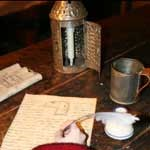 Hand writing on paper with quill pen on wooden desk. Also on the desk is a lantern, tin cup and inkwell.