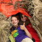 Suvival Camp campers celebrate in their debris hut.