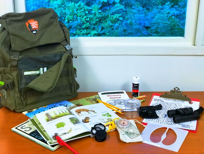 Backpack with scientific instruments and books on the table in front