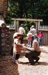 ranger helping young explorer try on buck skins