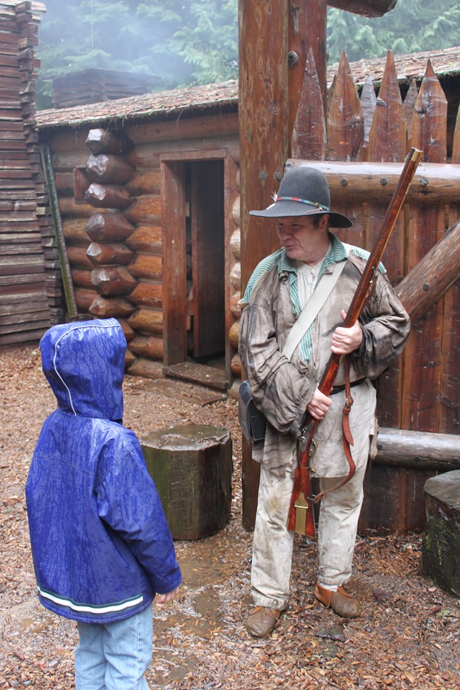 1805 costume ranger talking to a child in the rain.