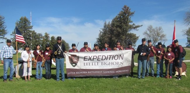 Students attending Expedition Little Bighorn pose for a photograph in front of Custer National Cemetery.