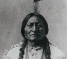 Black and white photograph of Sitting Bull with a single feather in his hair.