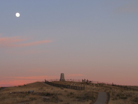 The memorial stands on top of Last Stand Hill. The photograph is taken at sunset with the moon shining in the top left corner.