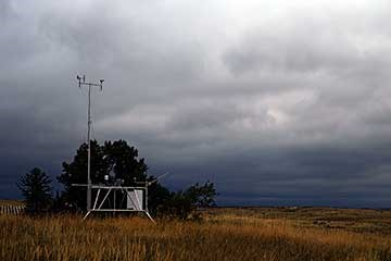 Weather station on the plains, in the fall,  sitting in front of a large green juniper tree.  The sky above is grey, blue, and white showing a storm moving in.