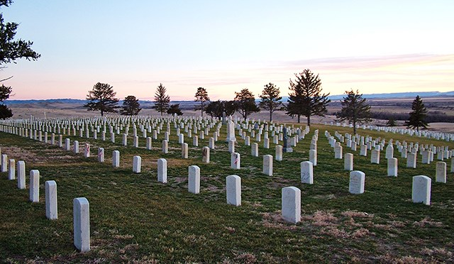 Photo of the Custer National Cemetery at sunset.  View is to the southwest and many rows of white headstones.