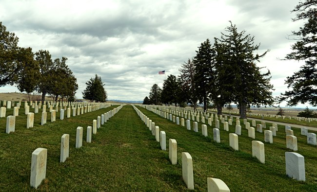 Photo of the Custer National Cemetery looking south.  Rows of white headstones are seen in the green grass.