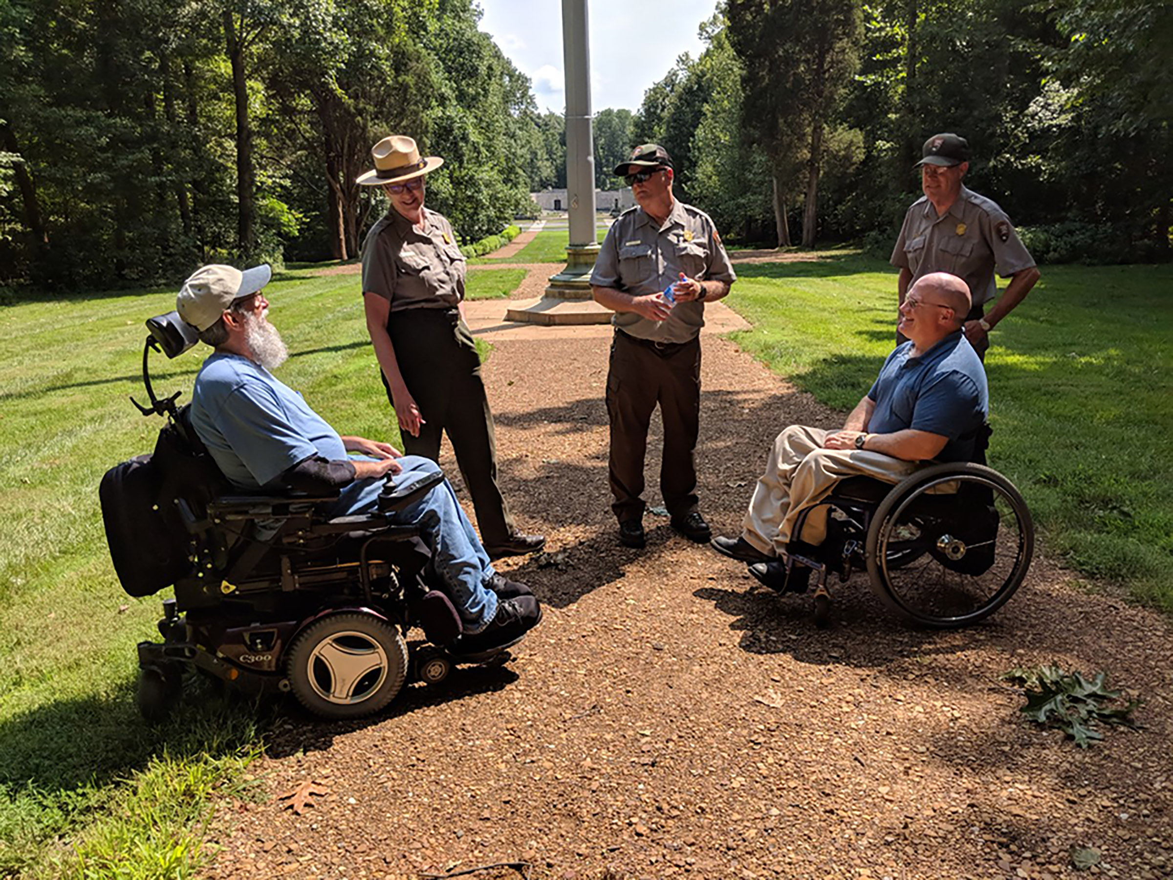 Two men in wheelchairs meet with Park Rangers on park trail.