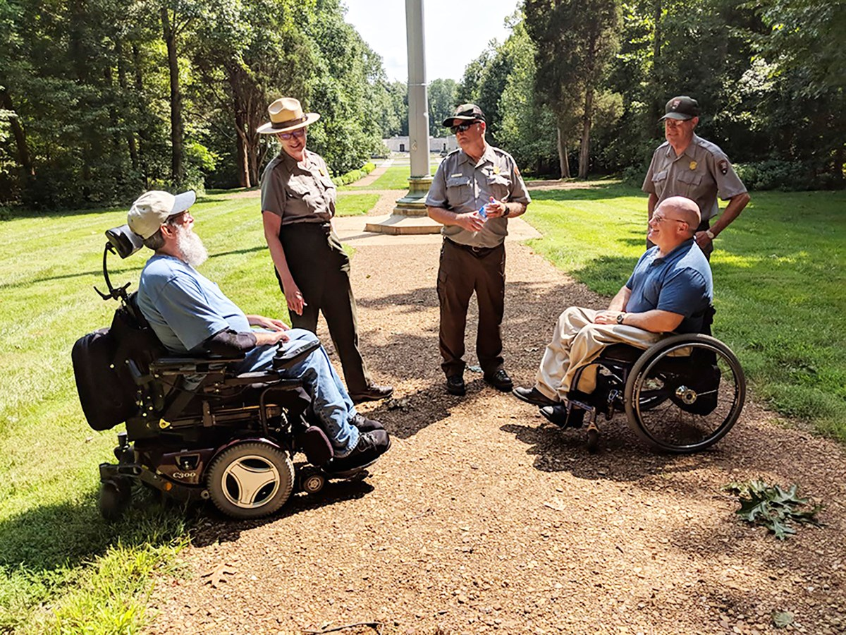 Two men in wheelchairs meet with Park Rangers on park trail