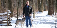 Visitor walking park trail with dog on leash