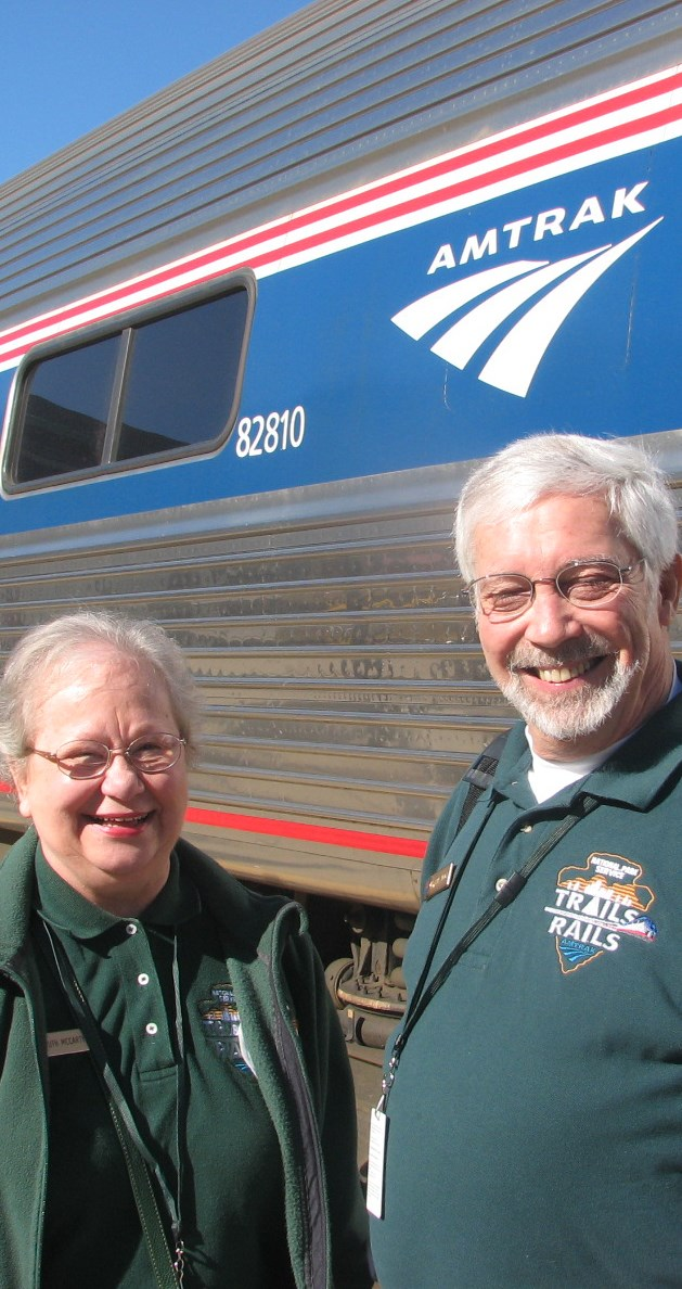 two trails and rails volunteers standing in front of a train