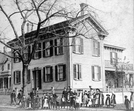 Students and adults in front of the Lincoln home, 1877.
