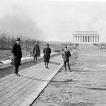 on left, men stand on drained lincoln memorial reflecting pool; memorial looms in right background, B&W