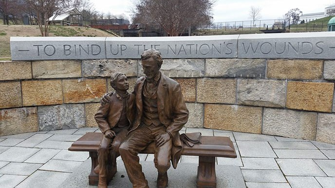 statue of abraham lincoln and son in bronze in front of curved stone wall