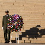 a park ranger stands with wreath at lincoln steps
