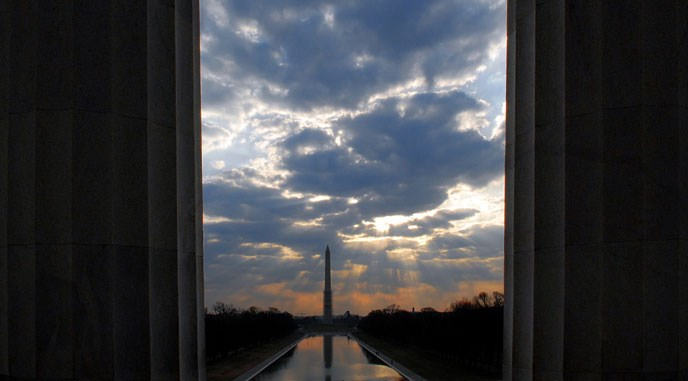 sunrise with washington monument in background, two columns in foreground on either side