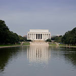 lincoln memorial in center on a sunny day reflected in the reflecting pool lined with green trees