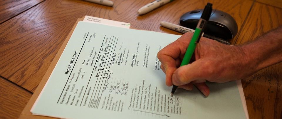 close up of a hand filling out a registration form
