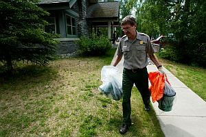 a park employee carries portable toilet cans in Denali National Park